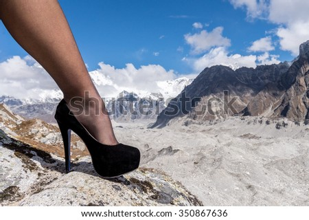 Women conquer the world: a female leg wearing high-heeled shoe against highest Himalayan Peaks (Cho Oyu mountain, 8,201 m) and glaciers