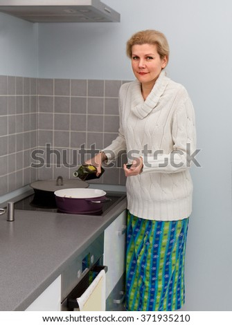 Women cooking food with olive oil at domestic kitchen - stock photo