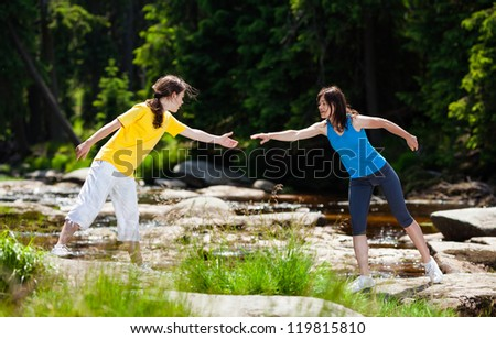 Women crossing river - stock photo
