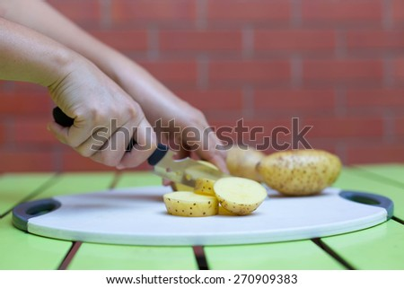 Women cutting  potato with knife on white broad