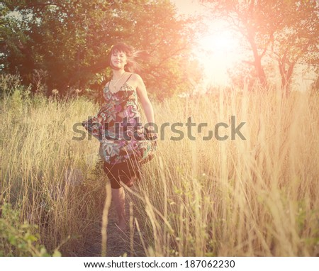 Women dancing in a high grass and smiling - stock photo