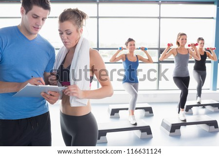 Women doing aerobics while trainer talking to woman in gym - stock photo
