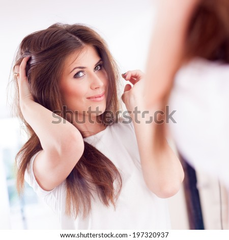 women doing hairstyle and look in the mirror
