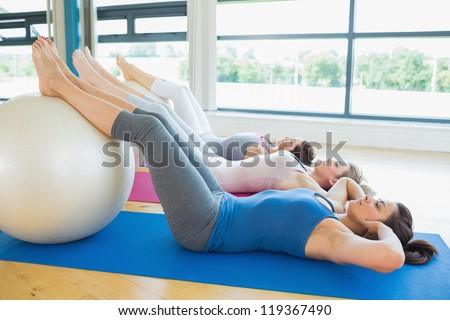 Women doing sit ups with exercise ball in fitnes studio - stock photo