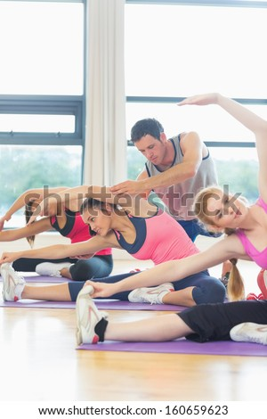 Women doing stretching exercise as trainer helps one at fitness studio