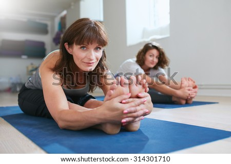 Women doing yoga together at gym, practicing paschimottanasana pose. Fitness female seated forward bend pose during training session. - stock photo
