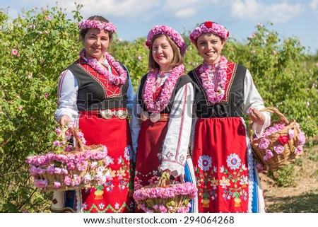 Women dressed in a Bulgarian traditional folklore costume picking roses in a garden, as part of the summer regional ritual in Rose valley, Bulgaria. - stock photo