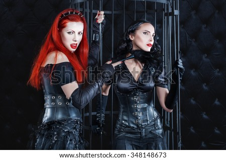 Women dressed in latex and leather dominate the game play. A woman in a dark room in the cell the prisoner.