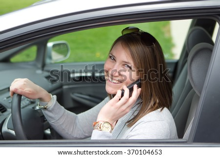 Women driving a car while looking at her cell phone smiling