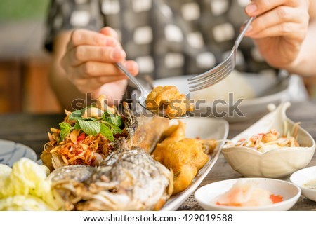 women eating fried fish in restaurant - stock photo