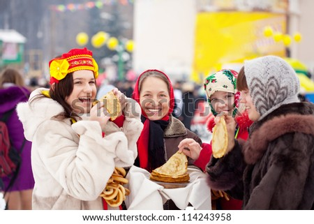 Women  eating pancakes during  Shrovetide in Russia