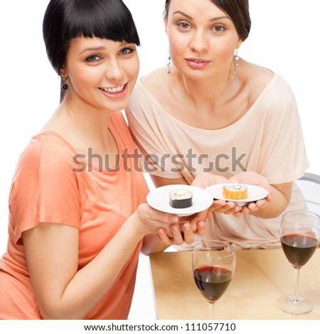 Women eating sushi rolls and drinking red wine - stock photo