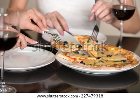 Women eats pizza. Close-up olives and cheese italian pizza with fork and knife and wine.