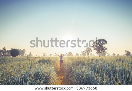 Women enjoying nature in meadow. Outstretched arms fresh morning air summer Field at sunrise. - stock photo