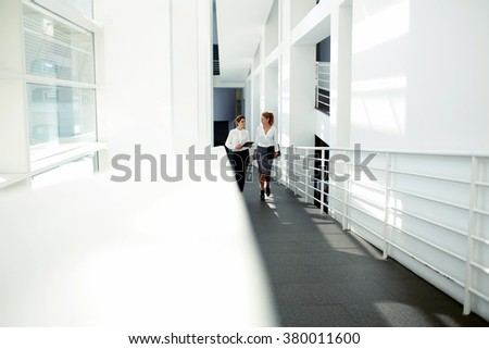 Women entrepreneurs with good mood discussing own work on digital tablet while walking in hallway of office interior, two cheerful female designers going to lunch after completion project on touch pad - stock photo