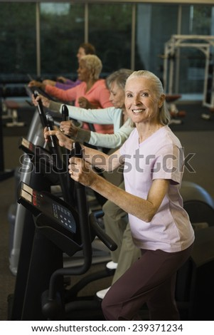 Women Exercising on an Elliptical Trainer - stock photo