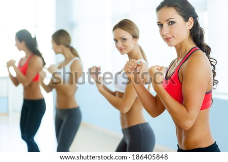 Women exercising. Two beautiful young women in sports clothing exercising and looking at camera - stock photo