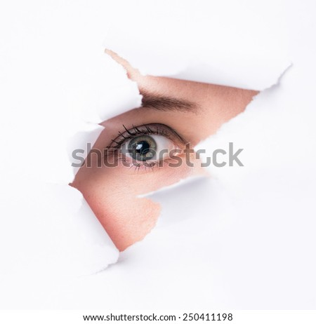 Women  eyes through a hole in a paper