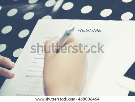Women fill out a resume for a job.