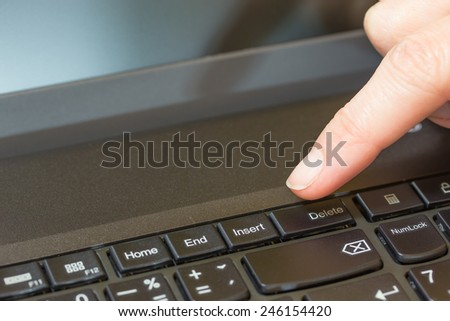 Women finger is ready to press the Delete key on the keyboard of a laptop.
