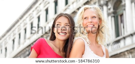 Women friends happy in Venice having fun smiling in street. Beautiful young Asian woman and Caucasian woman girlfriends on travel vacation, Piazza San Marco Square, Venice, Italy. - stock photo