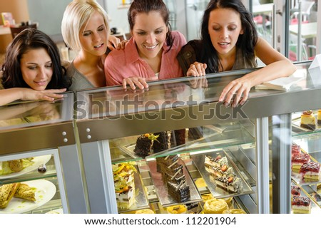Women friends looking at cakes in cafe craving window display - stock photo