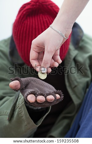 Women giving a coin for homeless poor man - stock photo