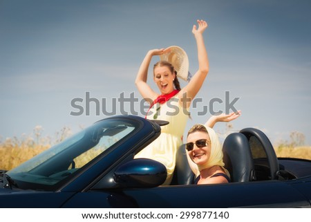 Women going in convertible car having fun on trip enjoying their freedom - stock photo