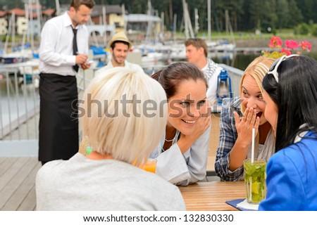 Women gossiping about men sitting at harbor bar summer terrace - stock photo