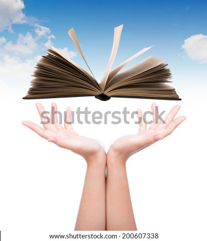 Women hand holding book over blue sky - stock photo