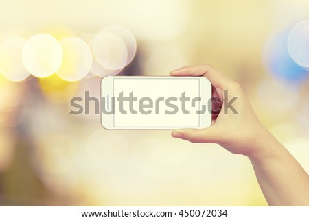 Women hand holding smartphone isolated white screen on abstract beautiful bokeh light background - stock photo