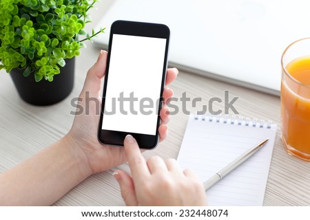 Women hand holding the phone with isolated screen above the desk  - stock photo