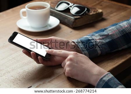 Women hand holding the phone with isolated screen above the desk and tea on the background - stock photo