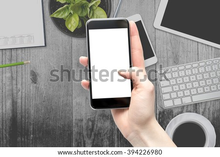Women hand holding the smartphone with isolated screen above the desk - stock photo
