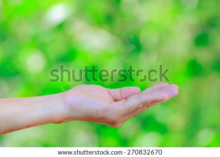 Women hand on blurred abstract green bokeh light background