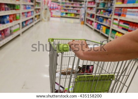 women hand push shopping cart  - stock photo