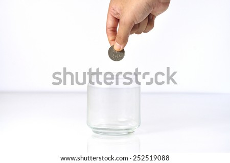 Women Hand Putting Coin Into Blank Glass Bottle, Selective Focus