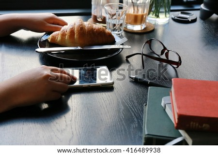 women hand use phone on breakfast time, croissants ,using mobile smart phone, Internet of things lifestyle with wireless communication and internet with smart phone.  - stock photo