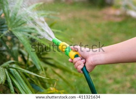 Women hand watering the lawn in the garden.