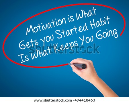 Women Hand writing Motivation is What Gets you Started Habit Is What Keeps You Going with black marker on visual screen. Isolated on blue. Business, technology, internet concept. Stock Photo