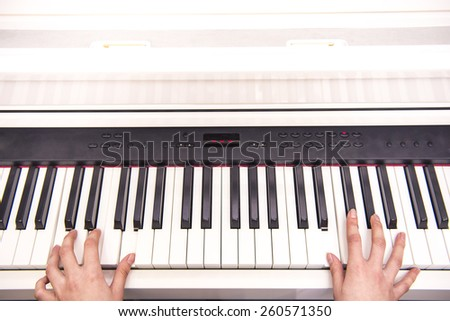 Women hands are playing the piano. Close-up. - stock photo