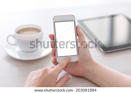 Women hands holding the white phone with isolated screen above the table with a cup of coffee and tablet - stock photo