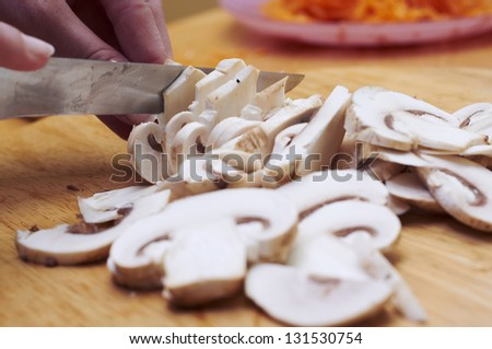 Women hands with knife cut the mushroom