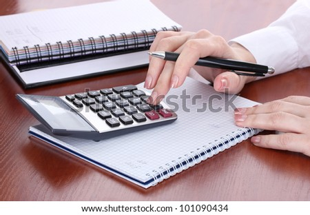 women hands with pencil, notebooks and Calculator on wooden table