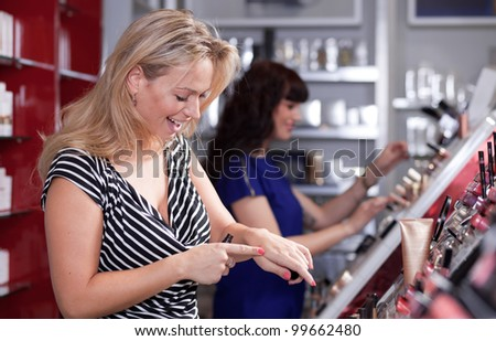 Women having fun while buying and testing cosmetics in a beauty store - stock photo