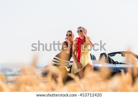 Women having joyride in convertible car having rest at grain field enjoying the landscape - stock photo