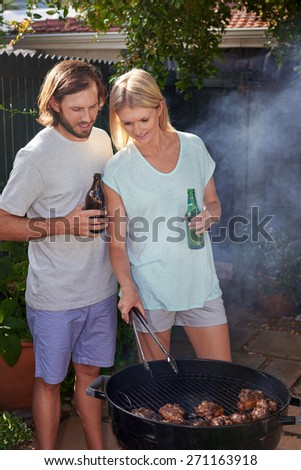 Women helping boyfriend husband at outdoor garden barbecue with tongs and beer - stock photo