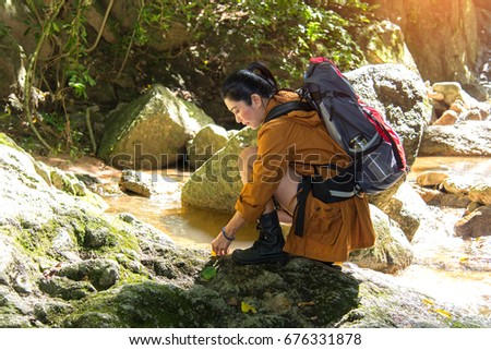 Women hiker with backpack checks map to find directions in wilderness area at waterfalls and forest. Travel Concept