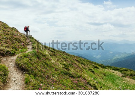 Women hiking with backpack holding trekking sticks high in the mountains covered with snow in summer. Landscape observation during a short break - stock photo