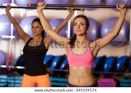 women holding body bars up they heads in the gym - stock photo